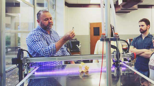 instructor standing at large format 3D printer